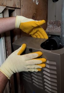 gloved hands working on heating system cabinet