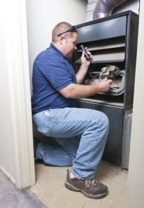 technician servicing the inside of a furnace