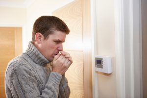 man wearing turtleneck looking very cold standing in front of a thermostat