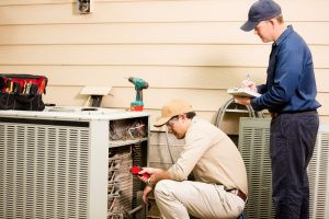technicians working on outside air conditioning unit