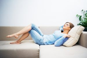 relaxed young woman laying on sofa in comfortable ac