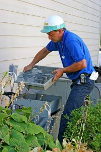technician accessing inside of air conditioning unit