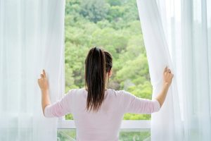 Rear view of a young woman opening the curtains in the morning