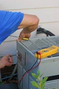 technician-working-on-outside-ac-unit