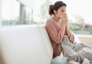 woman-sitting-on-her-couch-blowing-her-nose-in-tissue