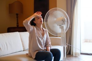 woman-using-fan-to-cool-down