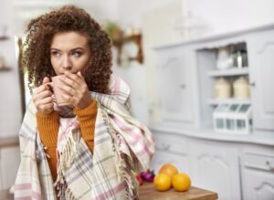 woman-huddled-under-blanket-drinking-from-mug