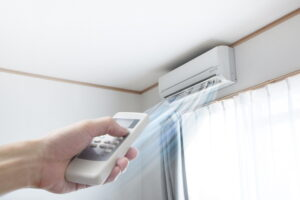 hand-using-remote-to-turn-on-ductless-air-handler