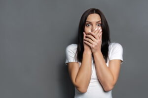 woman-looking-surprised-with-hands-covering-mouth